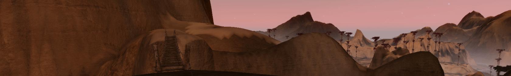 Narrow bridge across a deep ravine between arid tan peaks.